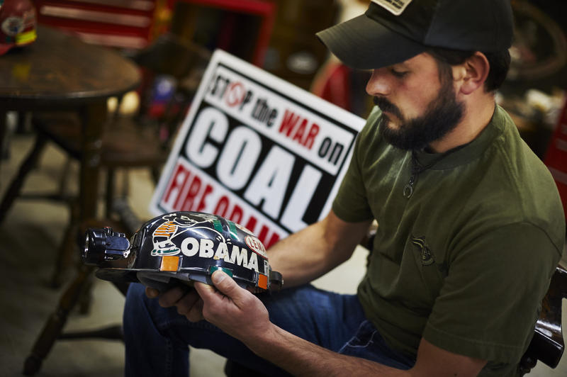 "Beltowski holds his helmet in his garage. The sign behind him reads ""Stop the war on coal. Fire Obama."""
