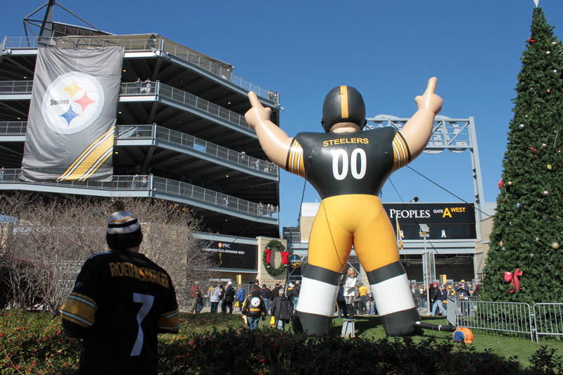 A giant, inflatable Steeler towers over the crowds filing into Heinz Field for a home game. The team's logo is displayed prominently to his left.