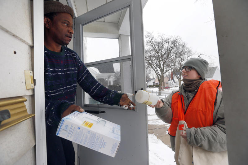 A Flint, MI resident receives water filters and a test kit from a Michigan National Guard Specialist.