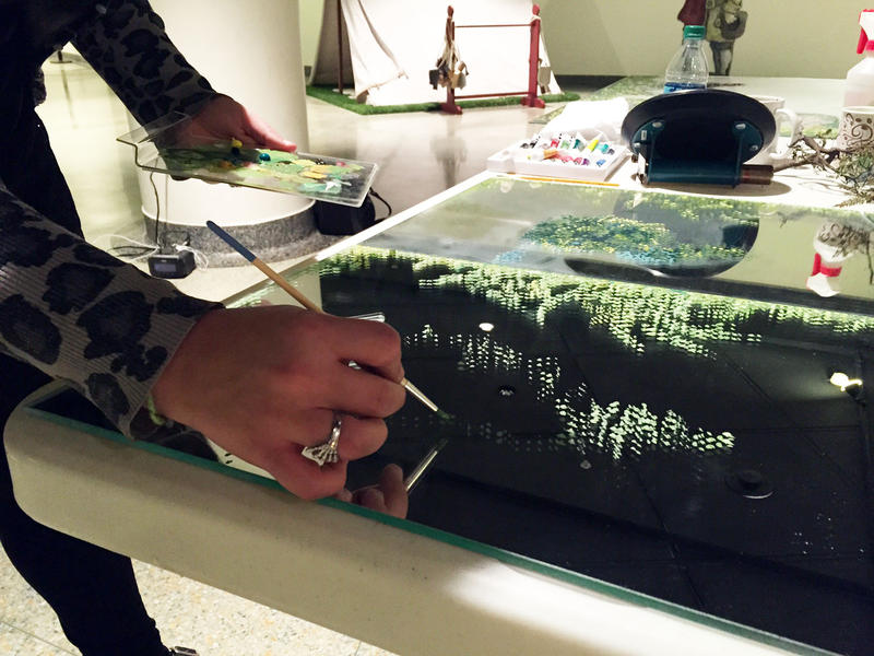 Megan Shalonis painstakingly paints each leaf of foliage in order to match an existing panel to be used in the Ft. Duquesne diorama.