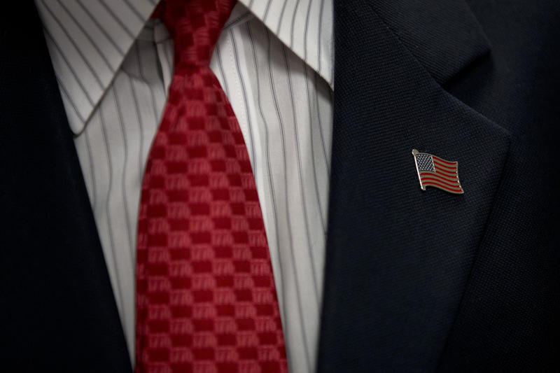 Political candidates continue to wear the flag pin originally created by Pittsburgh's Charles Orton, also known as XX Cough Drop Man.