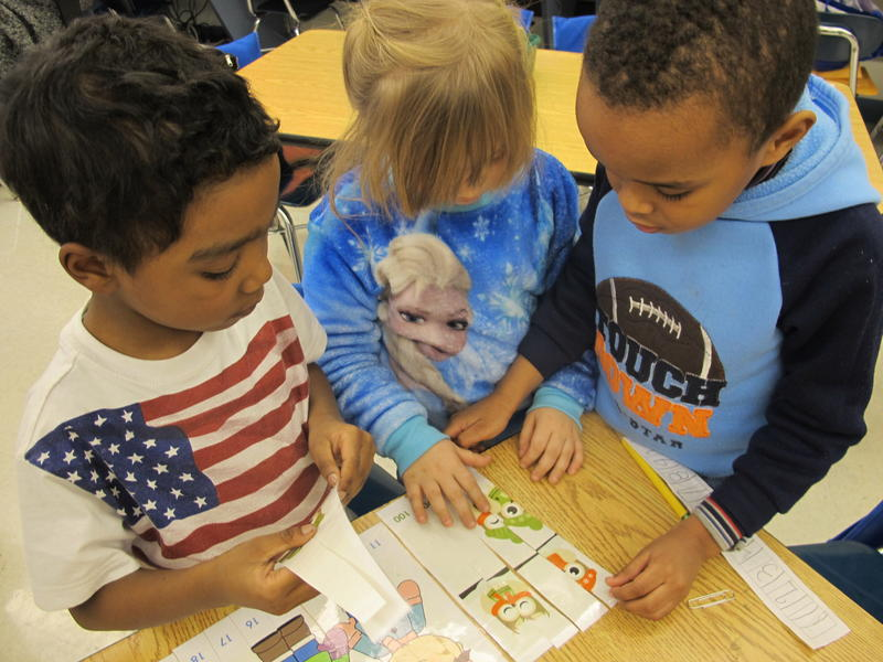 Kindergarteners Luis Hernandez, Kayla Gehlert and Jonathan Nicolas complete a number puzzle in Ms. Musyt's class. These three started with a puzzle that counted from 11-20, then moved up to counting by tens from 10-100. Other students began with 1-10