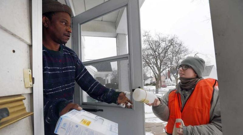 Louis Singleton receives water filters and a test kit from Michigan National Guard Specialist Jelena Tasevska Thursday, Jan. 21, 2015 in Flint, Mich.