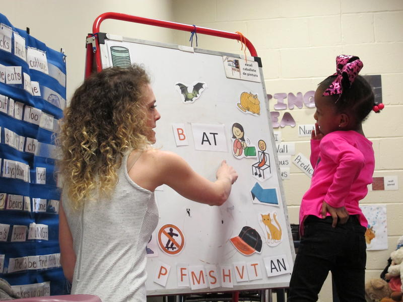"Teacher Erin Martin helps Harmoni Bacon sound out the word ""bat"" at the YWCA Homewood-Brushton Early Childhood Development and Education Center"