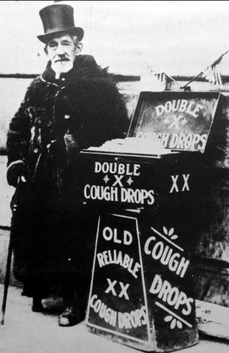 Charles Orton, Pittsburgh's XX Cough Drop man, stands beside his wares in downtown.