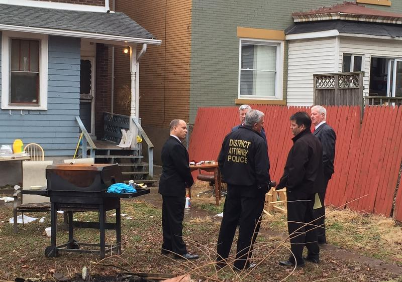 Allegheny County District Attorney Stephen Zappala and investigators survey the Wilkinsburg home where five people and an unborn child were killed.