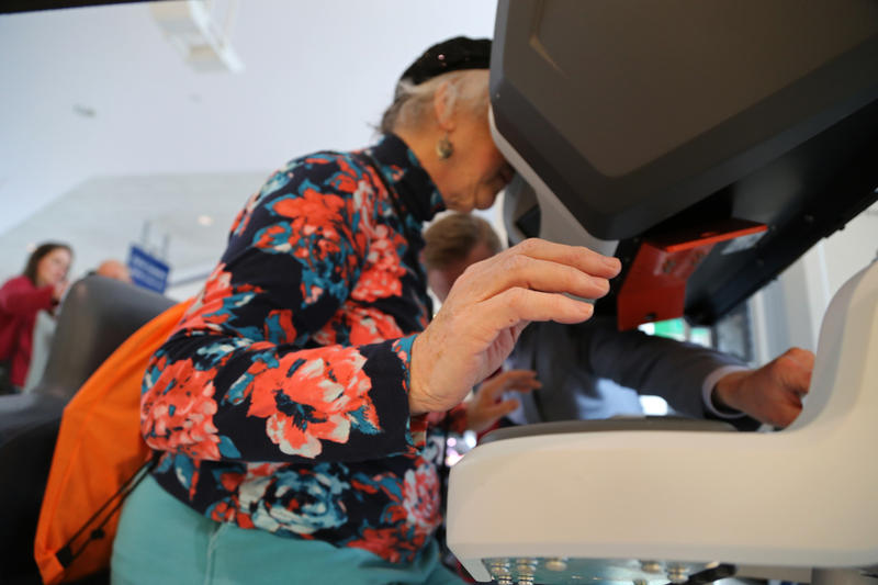 Carolyn Cornell Holland, 72, of Ligonier peeks through the viewfinder to try her prowess with the DaVinci Surgery Robot at the Westmoreland Mall on Thursday, March 24, 2016.