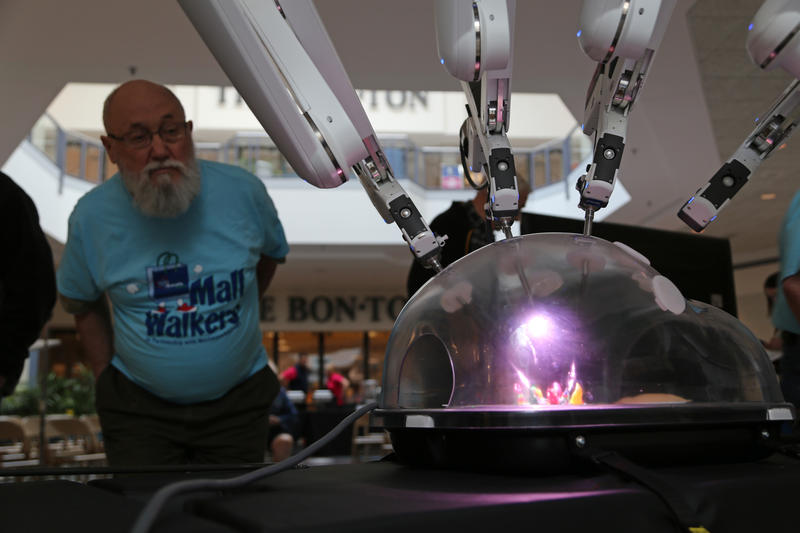 Monte Holland, 78, of Ligonier investigates the DaVinci Surgery Robot on display at the Westmoreland Mall on Thursday, March, 24, 2016.