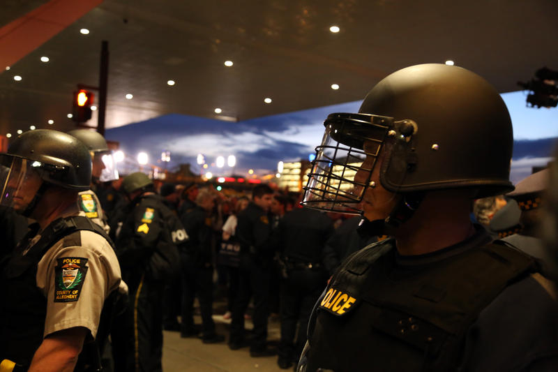 Officers in riot gear stand between supporters leaving Donald Trump's presidential campaign rally at the David L. Lawrence Convention Center and the protesters there to rebuke it.