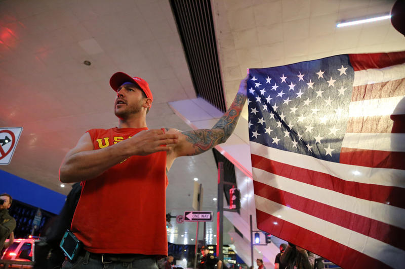 Brian Leek, 30, of Canonsburg waves an American flag in the face of protesters outside the David L. Lawrence Convention Center after Republican presidential candidate Donald Trump's first Pittsburgh rally on Wednesday, April 13, 2016.