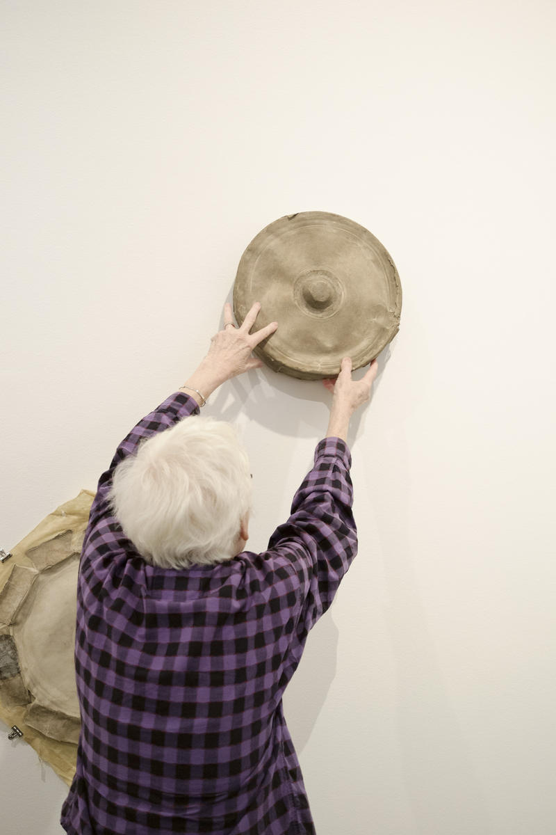 Artist Alison Knowles takes a 'bean chime' of hers off of a wall of the Carnegie Museum of Art.