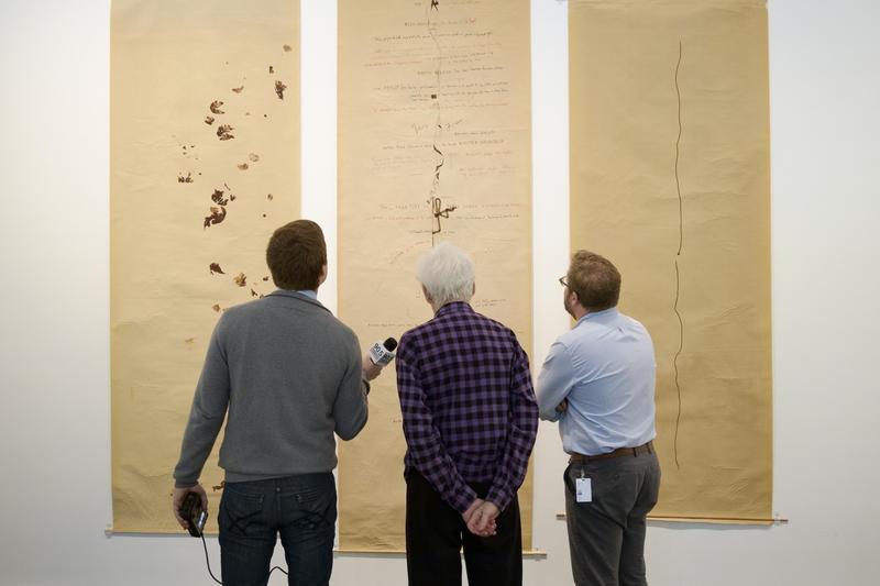 From left: Noah Brode, Alison Knowles and Eric Crosby examine a Knowles performance art score on display at the Carnegie Museum of Art.