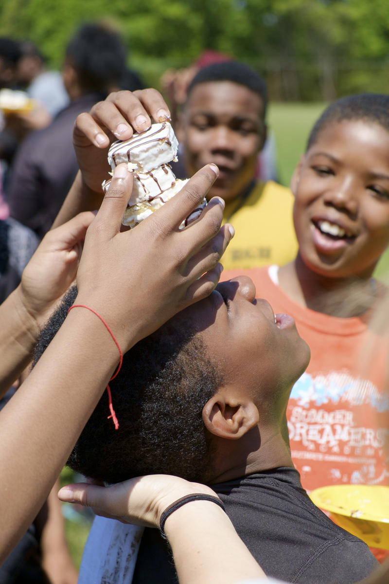 Carlos Brown (right) stacks zebra cakes on fellow sixth grader Tyrone Jones' head during a field day activity in North Park on Tuesday, May 24, 2016.