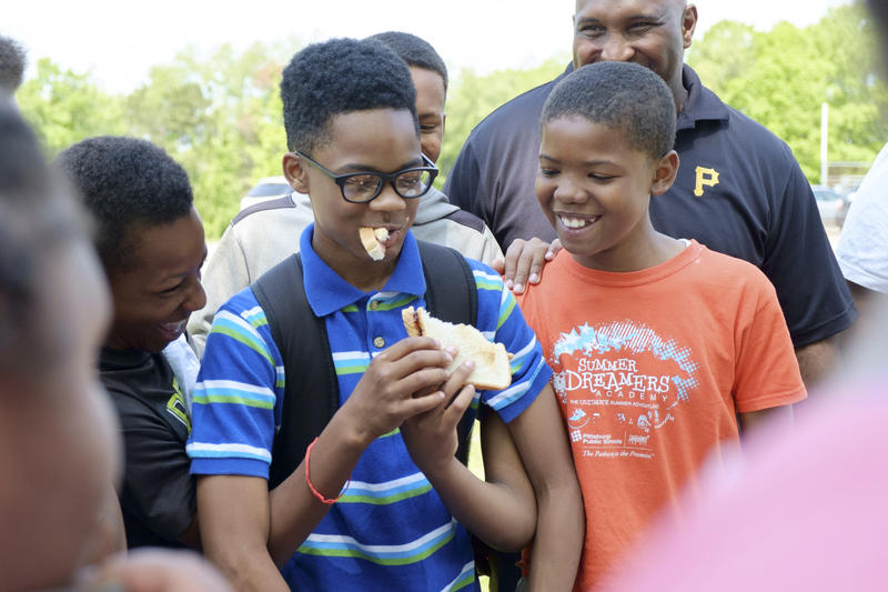 Erick Davis, a 13-year-old seventh grader from Wilkinsburg Middle attempts to eat a peanut butter and jelly sandwich as Tyrone Jones (left) and Carlos Brown (right), both 12-year-old sixth graders from Wilkinsburg's Turner Elementary, lend their hands.