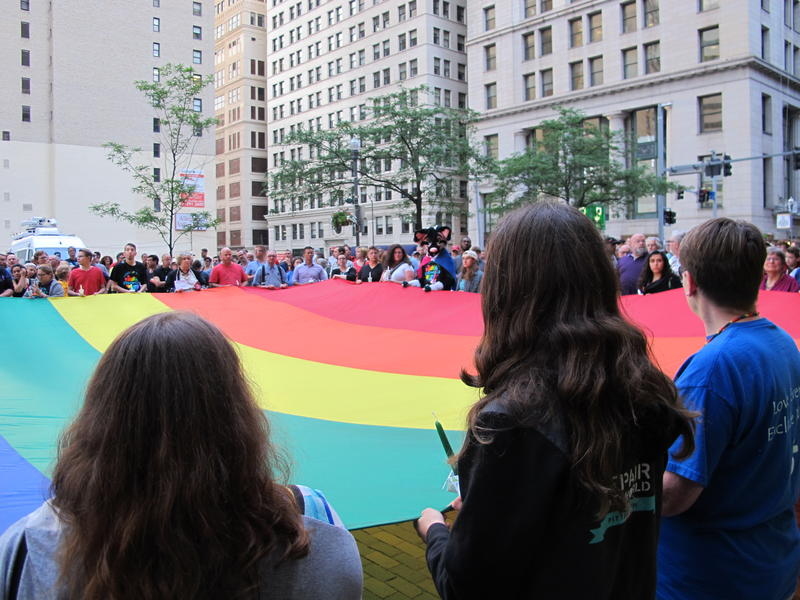 Mourners held a giant rainbow flag during Monday night's vigil in downtown Pittsburgh.