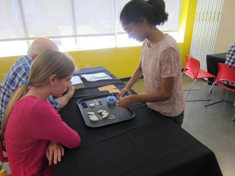 Fab Lab Volunteer Leader Nishka Edlabadkar helps workshop participants assemble 3-D prosthetic hands