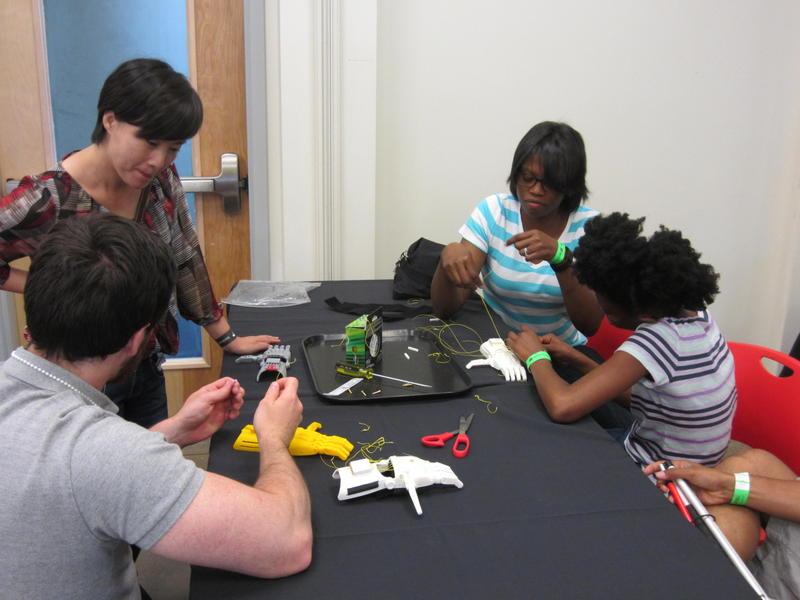 Fab Lab participants assemble a 3-D printed prosthetic hand