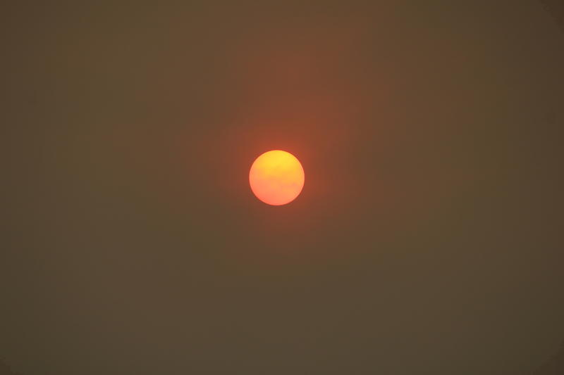 The morning sun over Pasadena, Calif. is reduced to an orange disk by smoke from a wildfire burning during an intense heat wave on Saturday, July 23, 2016.
