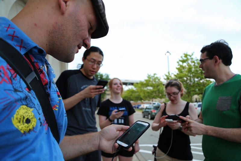 Tom Higgs, 33, tracks nearby Pokemon with friends outside P.F. Chang's at the Waterfront on Wednesday, July 13, 2016. Higgs said he meets friends at different points around town every night from 5 p.m. to as late as 1 a.m. playing the game.