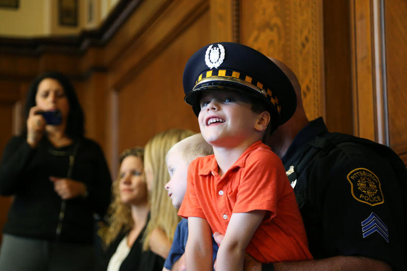 Callen Joyce, 5, of Beechview sits on the lap of his father Officer Mark Joyce at the Pittsburgh Bureau of Police promotion ceremony Monday, July 11, 2016.