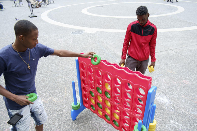 Cruz Wagner, of Garfield, and Jr. G, of the Hill District, play a game of Connect Four in Market Square as part of the Pittsburgh Downtown Partnership's initiative to bring more activity to the area.