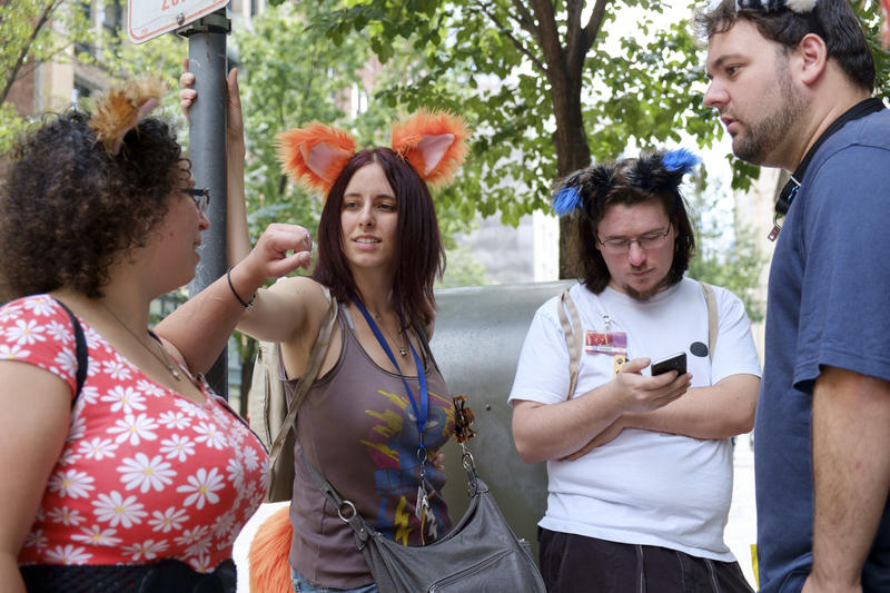 A group of furries from Connecticut discuss afternoon plans on Liberty Avenue during Anthrocon on Friday, July 1, 2016. Many Anthrocon attendees travel from out of state to take part in the annual convention.