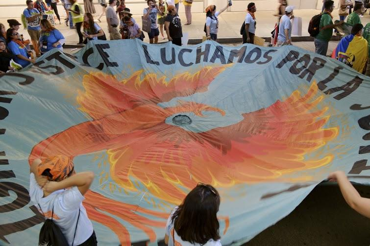 Activists unfurl a tarp emblazoned with a phoenix inside the David L. Lawrence Convention Center before a march Downtown on Friday, July 8, 2016.