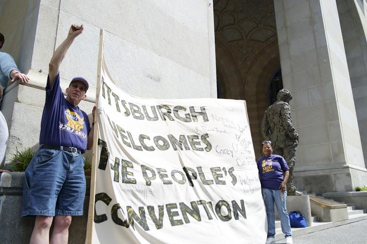 Service Employees International Union members wave a banner on the steps of the City County Building during a march by community organizations participating in the People's Convention on Friday, July 8, 2016.