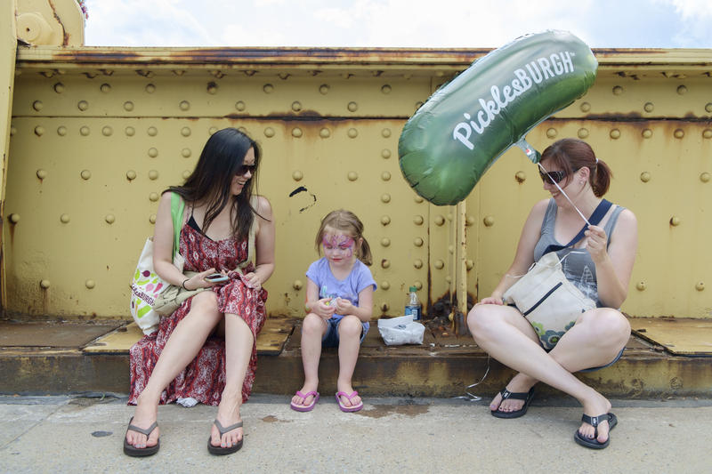 Kimberly Boyle, 35, Kae-Lynn Burks, 3, and Sara Snyder, 34, rest along the Rachel Carson Bridge after enjoying their first time at Picklesburgh on Friday, July 15, 2016.