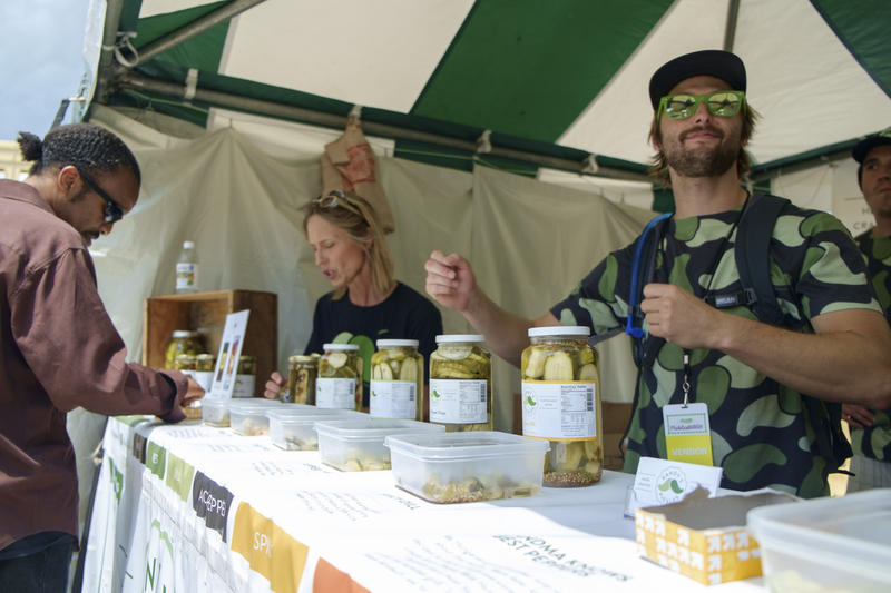 Andrew Rainey (right), owner of Randy's Pickles, invites attendees to sample his pickle flavors at Picklesburgh on Friday, July 15, 2016. Based out of Cleveland, Oh, it was the first time Rainey had participated as a vendor at the event.
