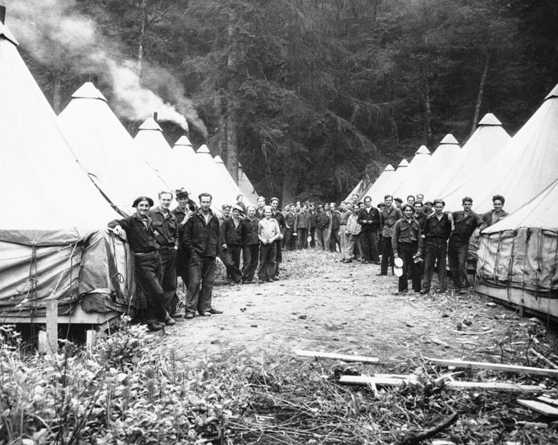 In heavy timber in Rainier National Park, Washington, Civilian Conservation Corps Company 930 members are at work at Tahoma Creek on July 3, 1933, on forest fire prevention, trail building and soil erosion as laid out by the National Park Service.