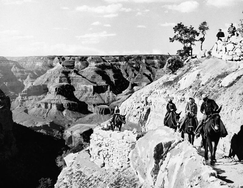 A group on horseback travel up a path at the Grand Canyon in Arizona, June 8, 1938.
