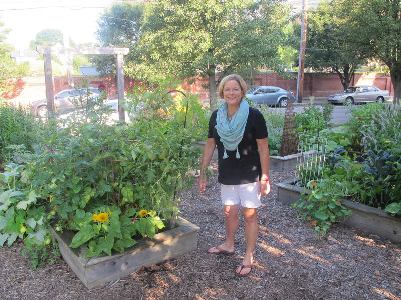 Kristin Hughes stands in the community garden she started in Friendship, after the apartment complex that was once housed on the lot burned down.