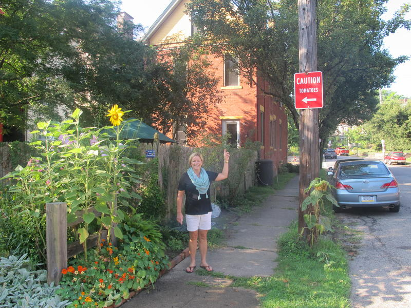 "Kristin Hughes points to a ""Caution, Tomatoes"" sign referencing her community garden in Friendship."
