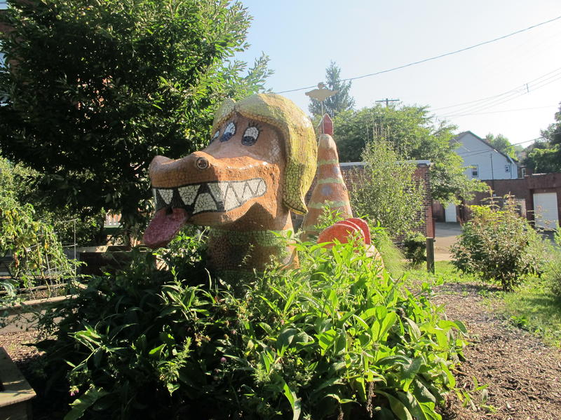 A sea serpent sculpture adorns the Friendship community garden.