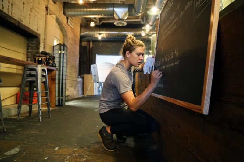 Chef Jessica Lewis, 30, of Lawrenceville readies a specials board before the lunch rush at Carota Cafe inside the Smallman Galley on Tuesday, Aug. 16, 2016.