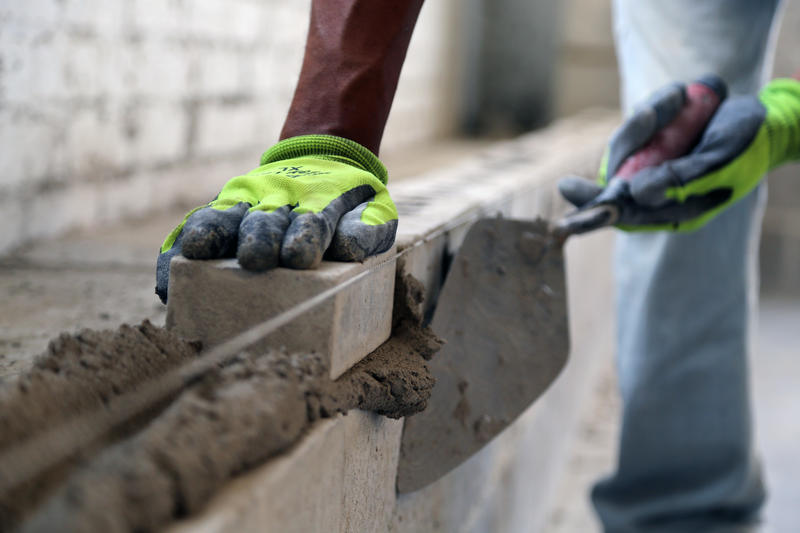 """Jeff Jackson, 28, scrapes excess mud off a line of bricks. Masonry is """"the foundation of my new beginning,"""" he said. """"If my boys see me getting up and going to work everyday, hopefully they'll follow my example. I don't want them to have the life I did."""""""