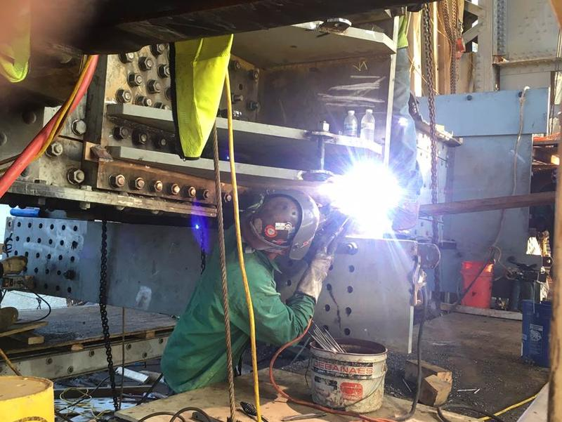 An ironwork welder works on a steel beam as part of the Liberty Bridge's jacking frame. PennDOT says they will not give a date for the structure's re-opening.