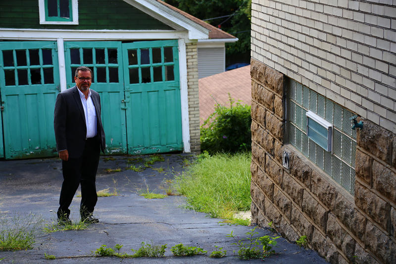 Mark Masterson, executive director of the Northside Community Development Fund, walks around a North Side home on Bonvue Street that was abandonded several years ago and is pegged for redevelopment.