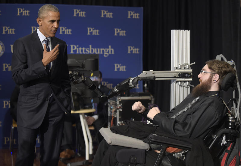 President Barack Obama talks with Nathan Copeland, right, during a tour of innovation projects at the White House Frontiers Conference at the University of Pittsburgh.