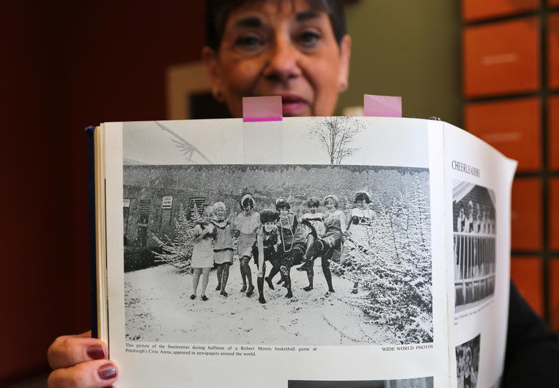 Valerie Miller, a Steelerette in 1964-65, holds up photograph of her cheer class near at a Robert Morris Junior College Basketball game. The girls were often used in promotional materials for the Steelerettes and RMJC.