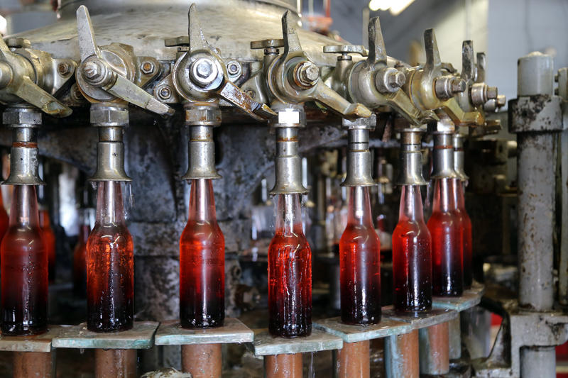 Bottles filled with cherry supreme soda pause along a decades-old conveyor manned by master bottler Steve Vokish at the Natrona Bottling Company in Natrona Heights on Wednesday, Sept. 14, 2016.