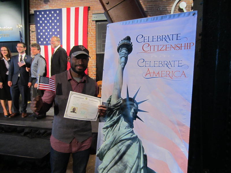 Omar Coker proudly displays his naturalization certificate and souvenir American flag.