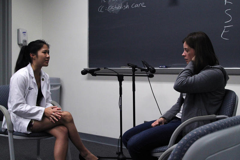 Stephanie Hum, 22, talks to Brandi Welle about Welle's character's medical symptoms during a standardized patient course at the University of Pittsburgh School of Medicine.