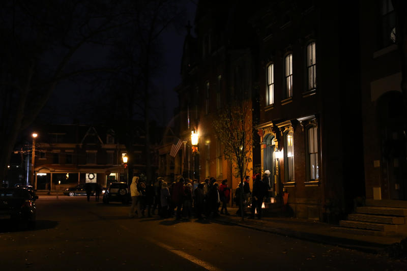 Attendees sing Christmas carols to announce their presence outside the 1871 home of Clayton Harris, who purchased the property in 2011. This is Harris' first foray into the neighborhood's Victorian home tour held annually in December.