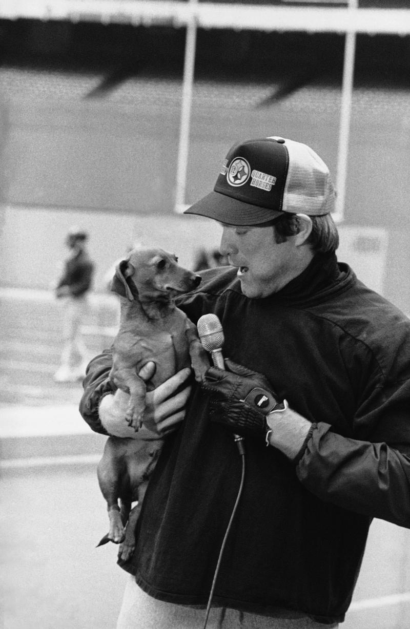 "Steelers' quarterback Terry Bradshaw ""interviews"" his pet dachshund during a practice session at Three Rivers Stadium, Dec. 29, 1979. Bradshaw was being interviewed by a TV crew ahead of the AFC playoff game against Miami, when the taping went awry."