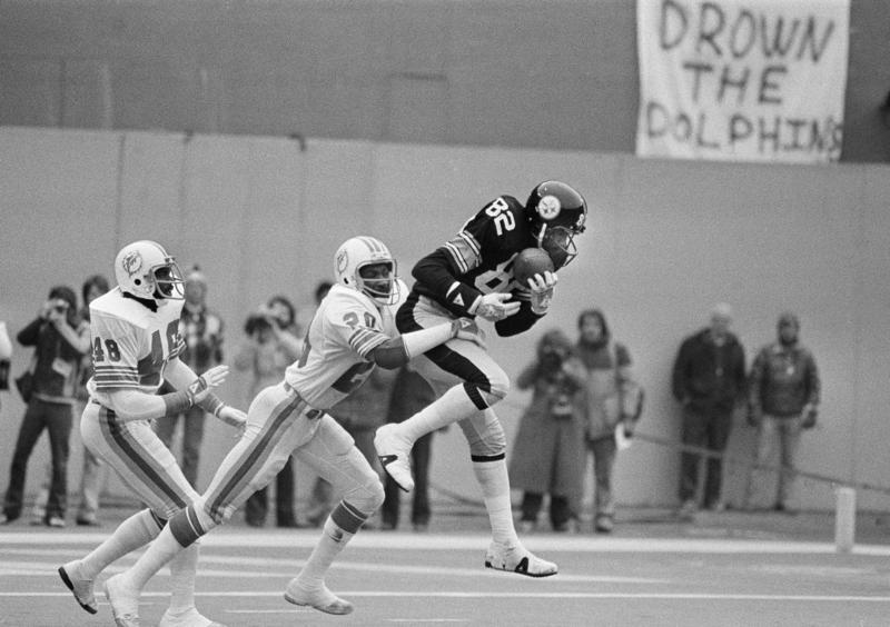 Pittsburgh Steeler John Stallworth leaps to catch a pass from Terry Bradshaw for the Steelers second touchdown in an AFC game against Miami, Dec. 31, 1979. Dolphin Neal Colzie (20) fell short.