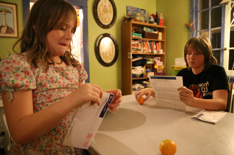 Emmaline Thompson, left, and Duncan Rieger, right, open letters from the Pittsburgh Public School District notifying them of their acceptance to magnet schools.