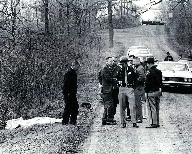 Washtenaw County Sheriff's officers confer on a rural road north of Ypsilanti where the body of a 13-year-old girl was found in 1969.