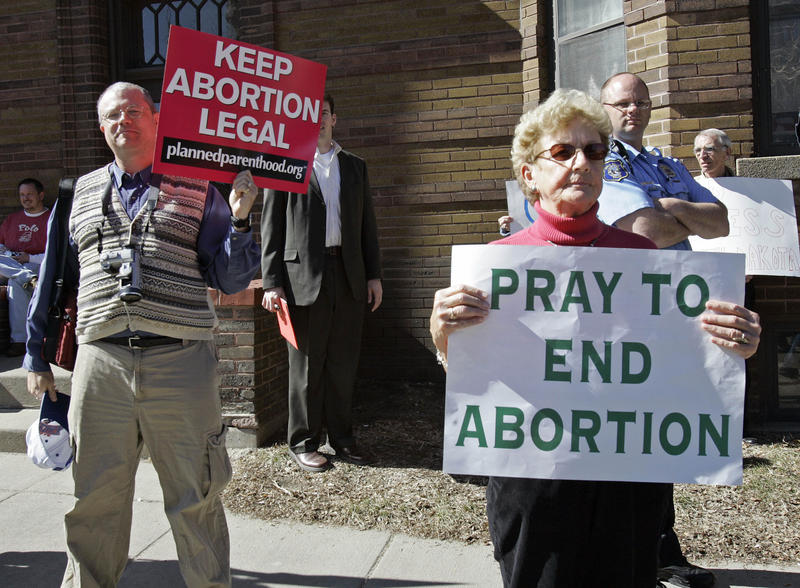 Demonstrators, one pro-choice, the other, pro-life, holds up signs during a protest in reaction to South Dakota's anti-abortion law, outside the Federal Court building in downtown Sioux Falls, S.D., Thursday, March 9, 2006.